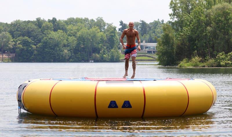 Homem bonito considerável que salta em um trampolim da água que flutua em um lago em Michigan durante o verão imagens de stock