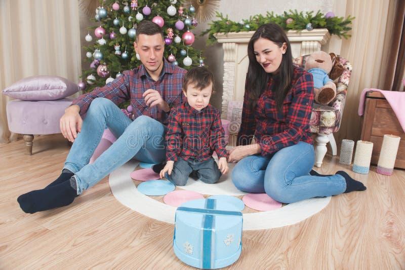 Homem bonito da família e fêmea novos com o bebê na véspera dezembro do Xmas imagens de stock royalty free