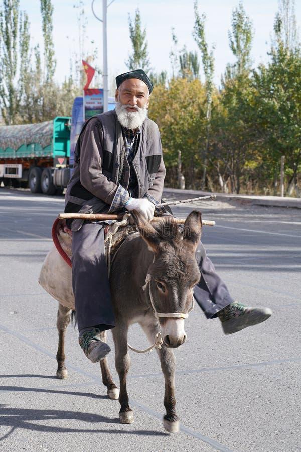 Homem bonito idoso de Uygur que monta um dongkey bonito pequeno foto de stock