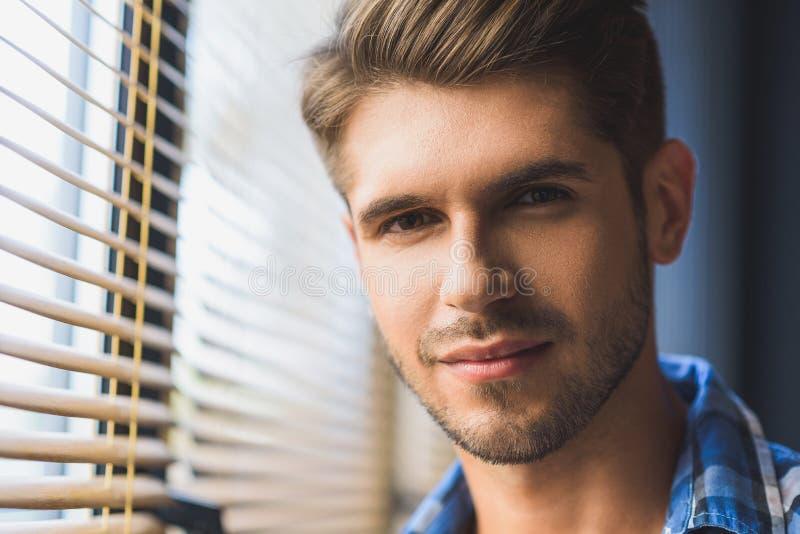 Homem bonito na frente de uma janela imagens de stock