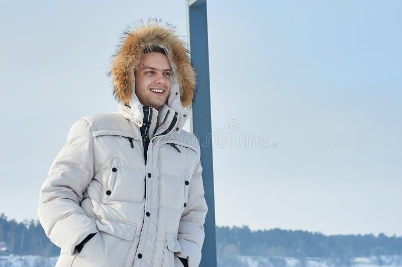 Homem bonito novo em um revestimento branco com a capa da pele no inverno Sibéria Retrato da forma foto de stock