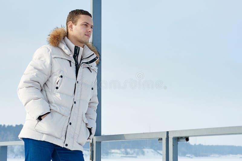 Homem bonito novo em um revestimento branco com a capa da pele no inverno Sibéria Retrato da forma imagem de stock