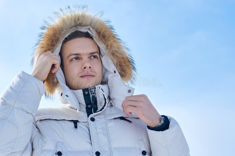 Homem bonito novo em um revestimento branco com a capa da pele no inverno Sibéria Retrato da forma imagens de stock