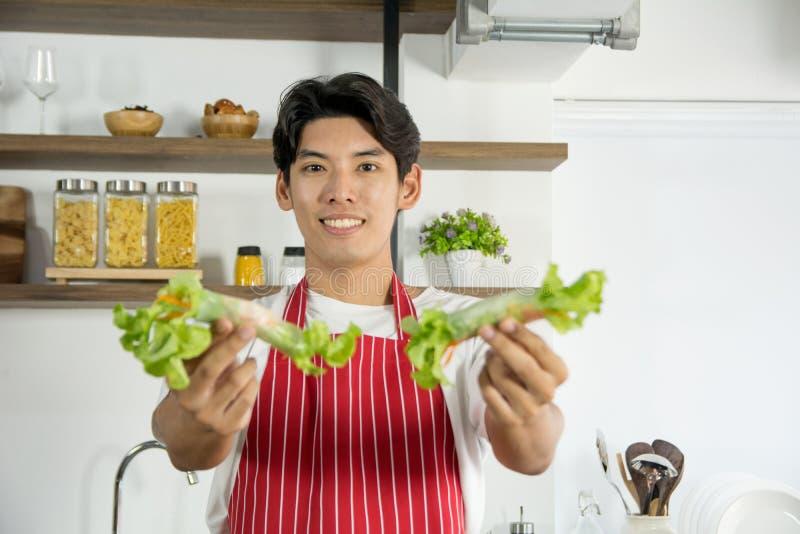 Homem bonito novo no avental vermelho que apresenta o menu saudável do rolo da salada com sorriso e os povos bem-vindos para prov fotos de stock royalty free