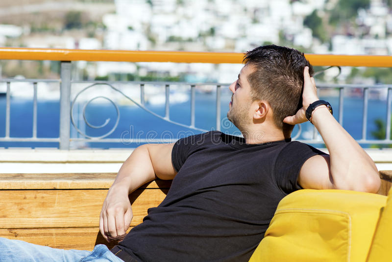Homem bonito novo que relaxa e que olha o mar azul foto de stock