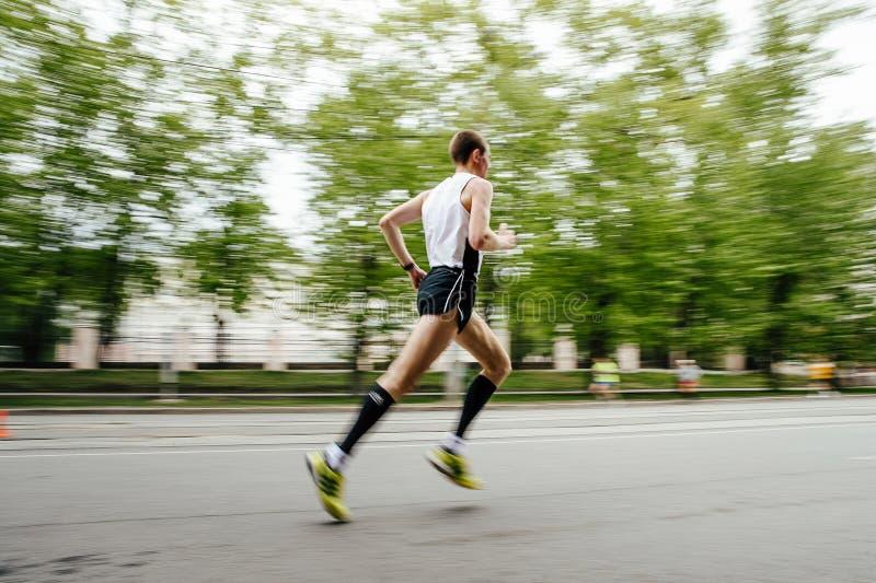 Homem borrado do corredor do movimento que corre na rua da cidade fotografia de stock royalty free