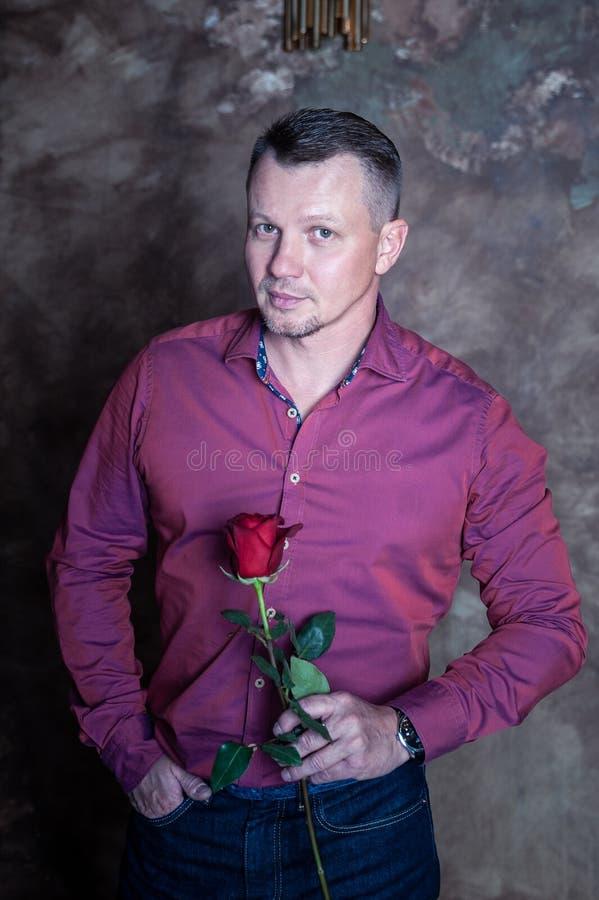 Homem branco agradável com uma rosa vermelha em suas mãos, olhando a câmera imagens de stock