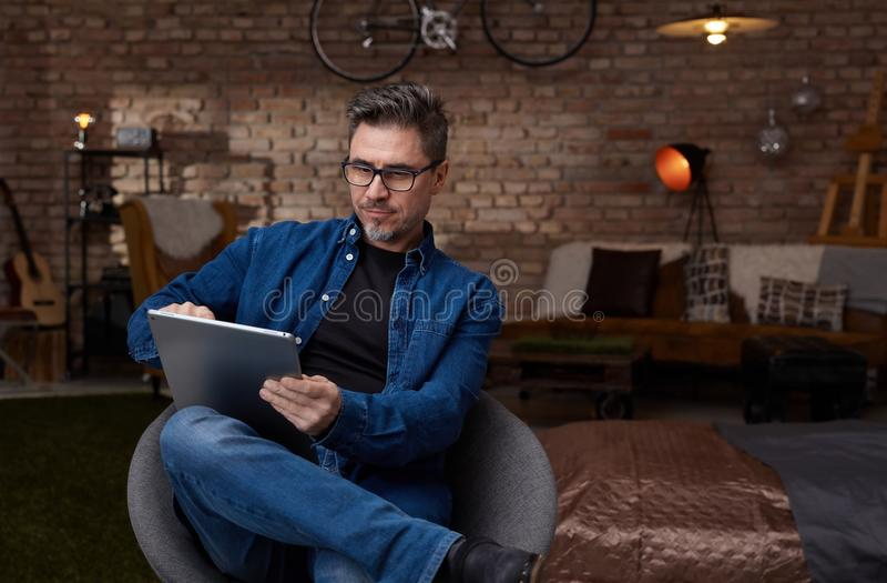 Homem branco mais idoso que senta-se na sala escura usando a tabuleta imagens de stock