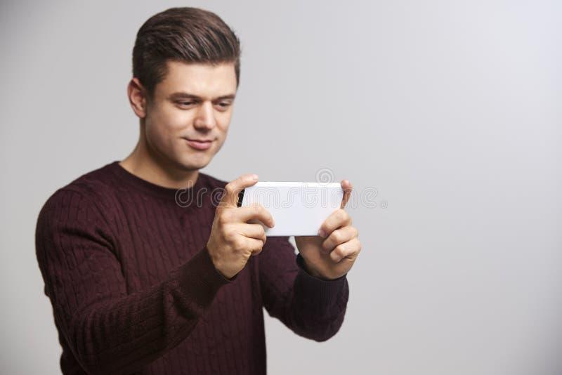 Homem branco novo que toma um selfie com seu smartphone fotos de stock