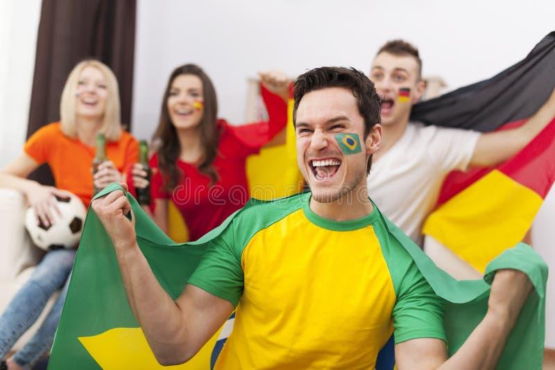 Homem brasileiro com seu cheering dos amigos imagem de stock