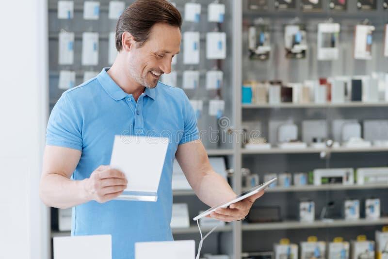 Homem brilhante que usa a tabuleta digital na loja da eletrônica fotos de stock