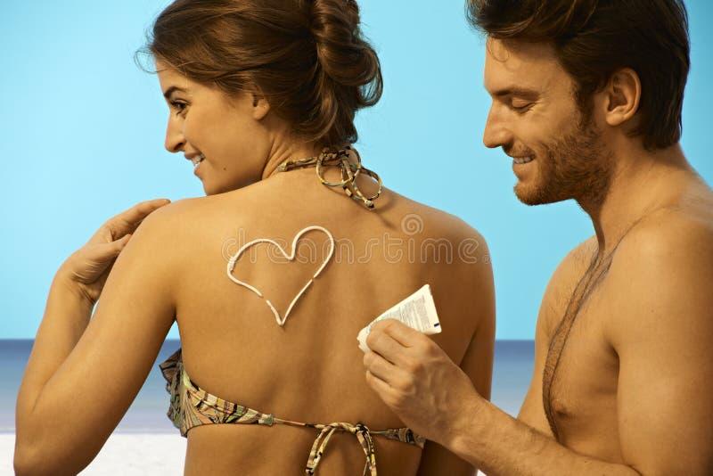 Homem brincalhão que põe o creme do sol sobre a mulher no roupa de banho fotografia de stock royalty free