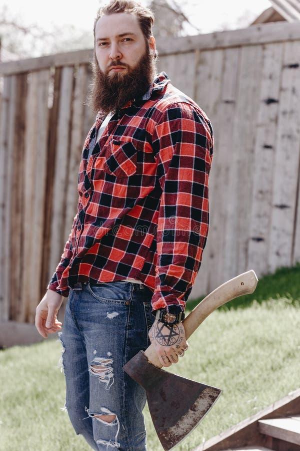 Homem brutal forte com uma barba vestida em uma camisa verificada e em umas calças de brim rasgadas que anda com um machado nas m imagem de stock royalty free