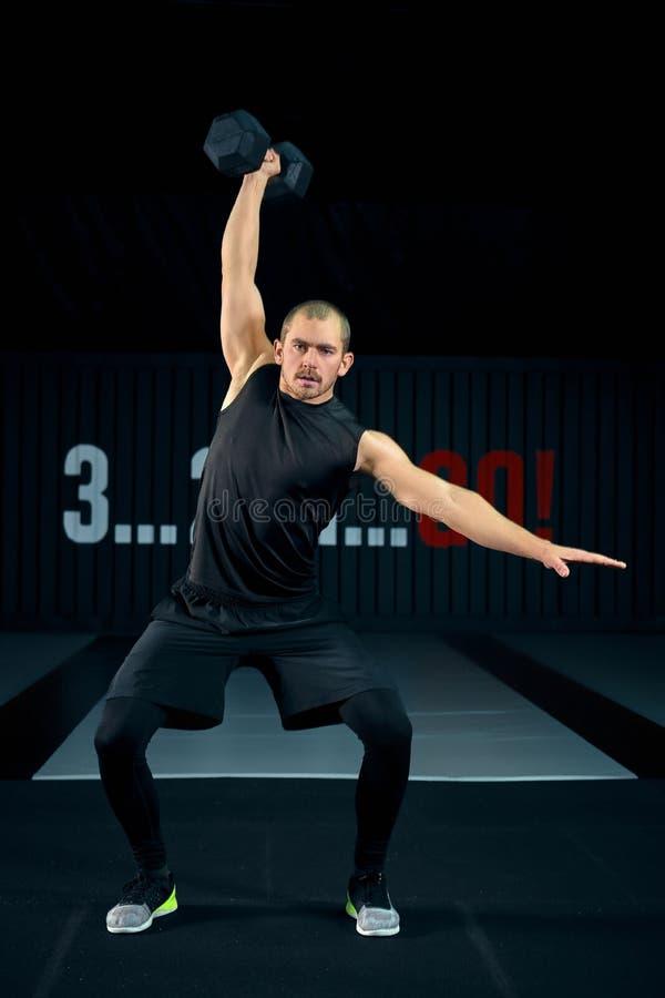 Homem brutal forte que faz ocupas com peso no gym, foto completa do comprimento Indivíduo que faz exercícios com peso dentro imagens de stock royalty free