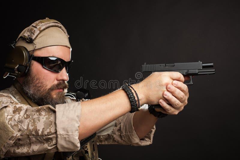 Homem brutal no uniforme e na armadura militares do deserto que estão em uma cremalheira de combate e que apontam de sua arma em  fotografia de stock