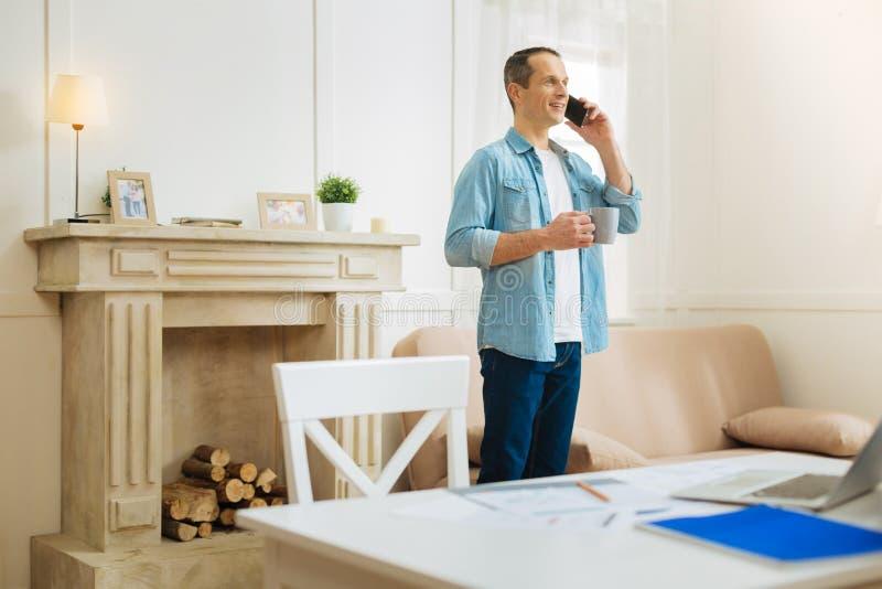 Homem calmo agradável que fala no telefone ao estar em sua sala bonita fotografia de stock