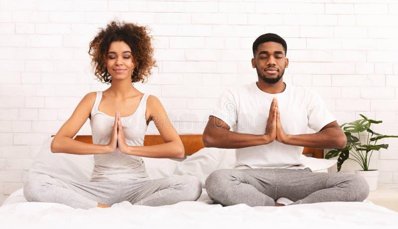 Homem calmo e mulher africanos que meditam na posição do namaste sobre a cama imagem de stock royalty free