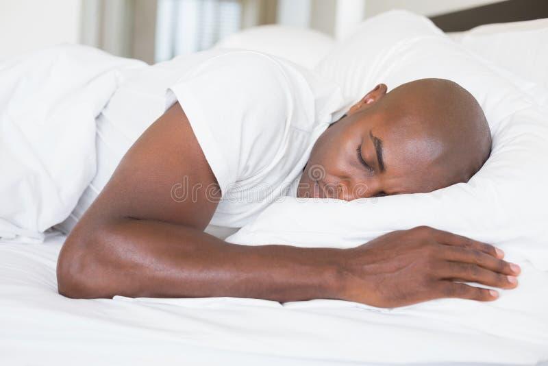 Homem calmo que dorme na cama imagem de stock