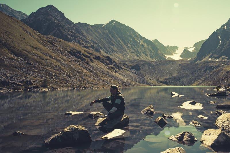 Homem calmo que senta-se em uma rocha nas férias que olham o lago e as montanhas na noite do verão Kucherlinskoe do lago altai En foto de stock royalty free