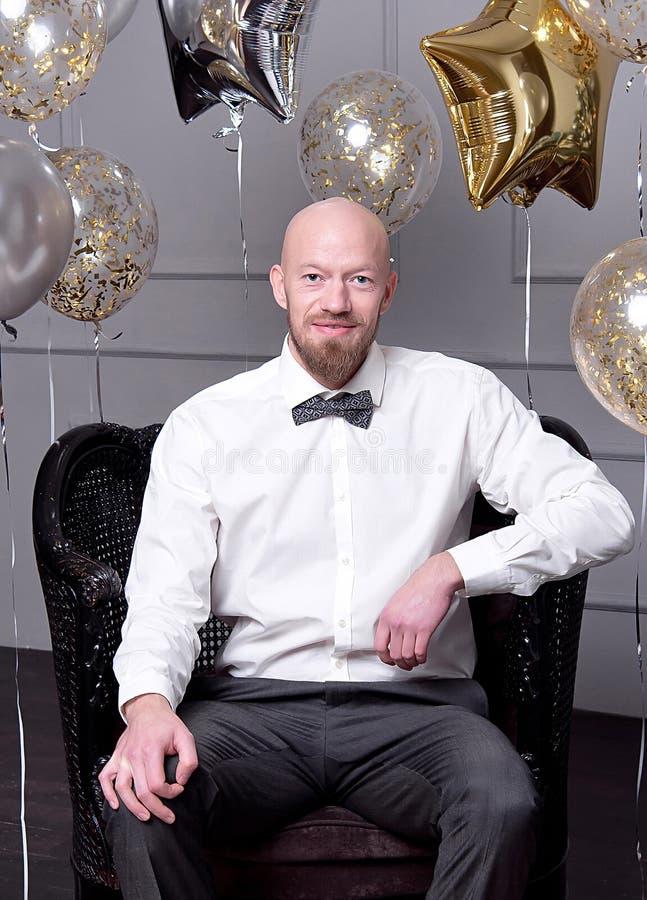 Homem calvo atrativo com uma barba que comemora com balões e confetes fotografia de stock