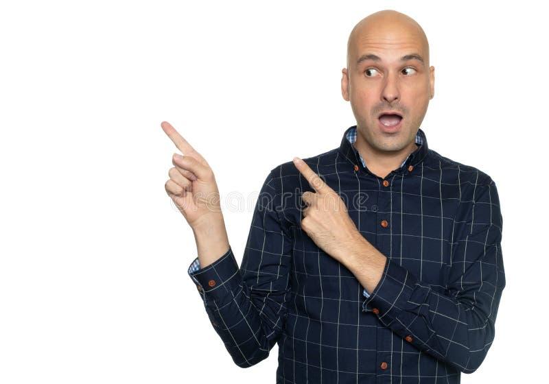 Homem calvo chocado que aponta os dedos de lado Isolado imagens de stock royalty free