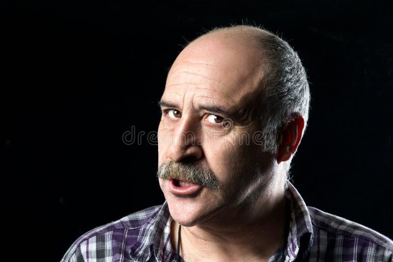 Homem calvo com os bigodes muito irritados foto de stock