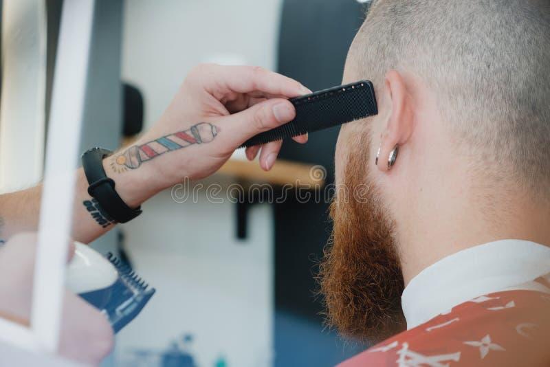 Homem calvo farpado considerável no barbeiro O barbeiro corta o cabelo com fotografia de stock royalty free