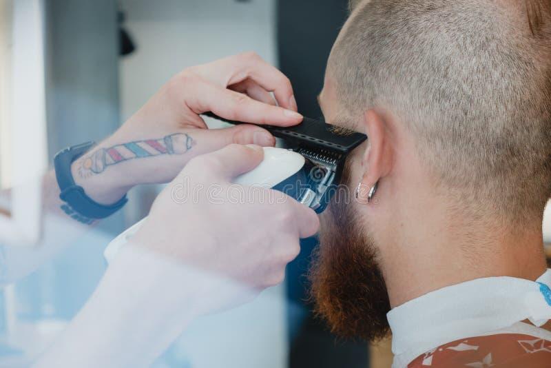 Homem calvo farpado considerável no barbeiro O barbeiro corta o cabelo com foto de stock