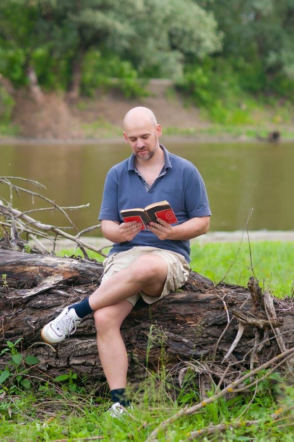 Homem calvo feliz que lê o livro foto de stock