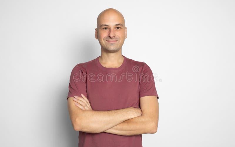 Homem calvo ocasional seguro que sorri com os braços cruzados imagem de stock