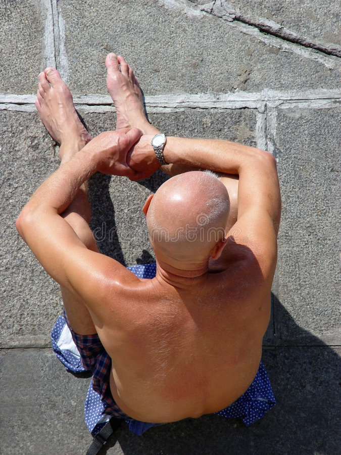 Homem calvo que sunbathing imagem de stock