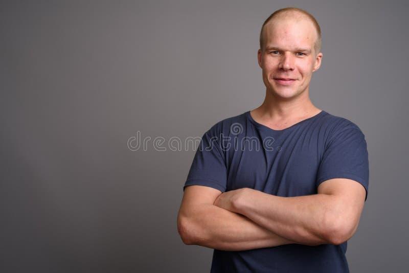 Homem calvo que veste a camisa azul contra o fundo cinzento fotografia de stock royalty free
