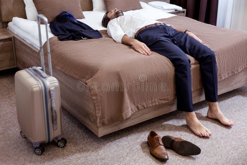 Homem cansado considerável que vem ao hotel imagem de stock
