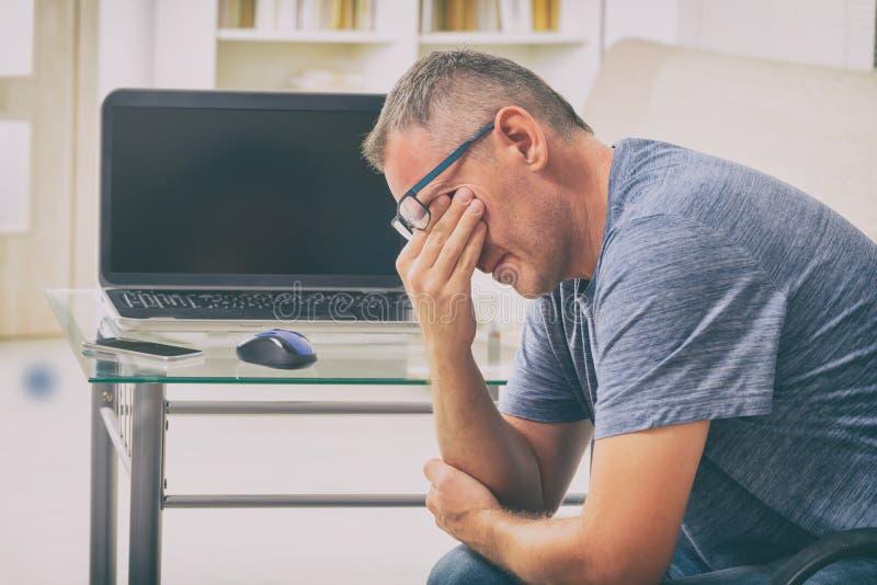 Homem cansado do freelancer que fricciona seus olhos fotos de stock royalty free