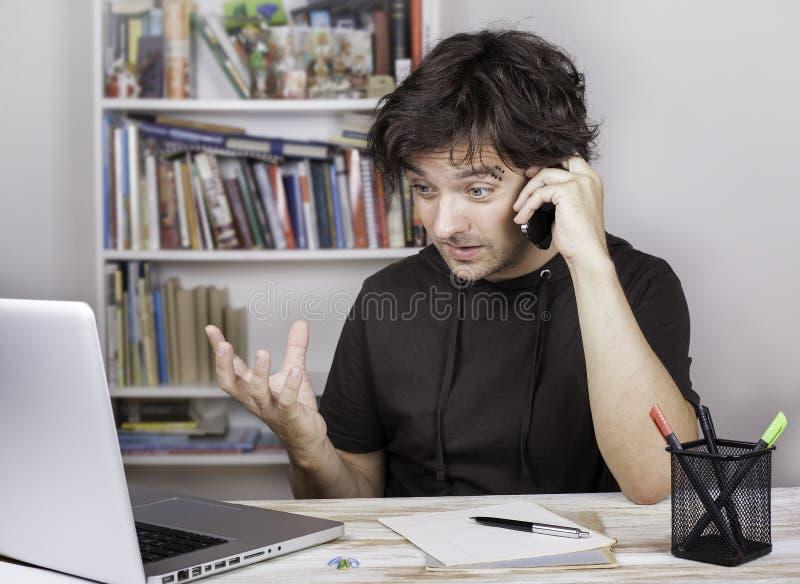 Homem cansado e irritado que fala no telefone celular imagens de stock royalty free