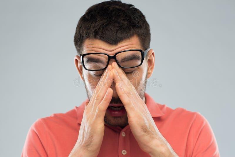Homem cansado nos monóculos que friccionam os olhos imagens de stock