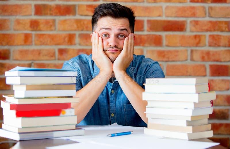 Homem cansado novo com livros em uma tabela fotos de stock royalty free
