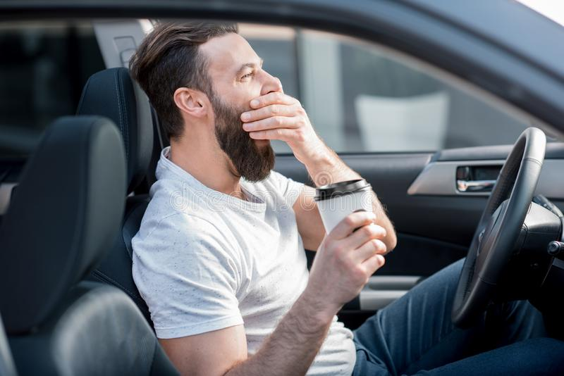 Homem cansado que conduz um carro imagens de stock