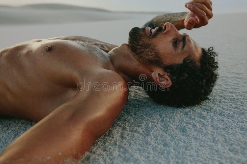 Homem cansado que descansa após o exercício no deserto foto de stock