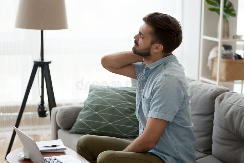 Homem cansado que faz massagens o sofrimento do pescoço do estilo de vida sedentariamente fotos de stock royalty free