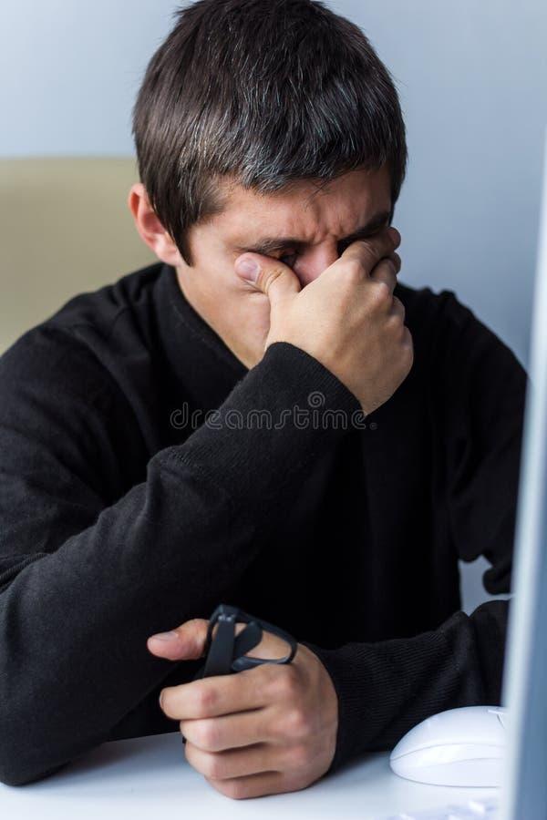 Homem cansado que fricciona seus olhos imagens de stock