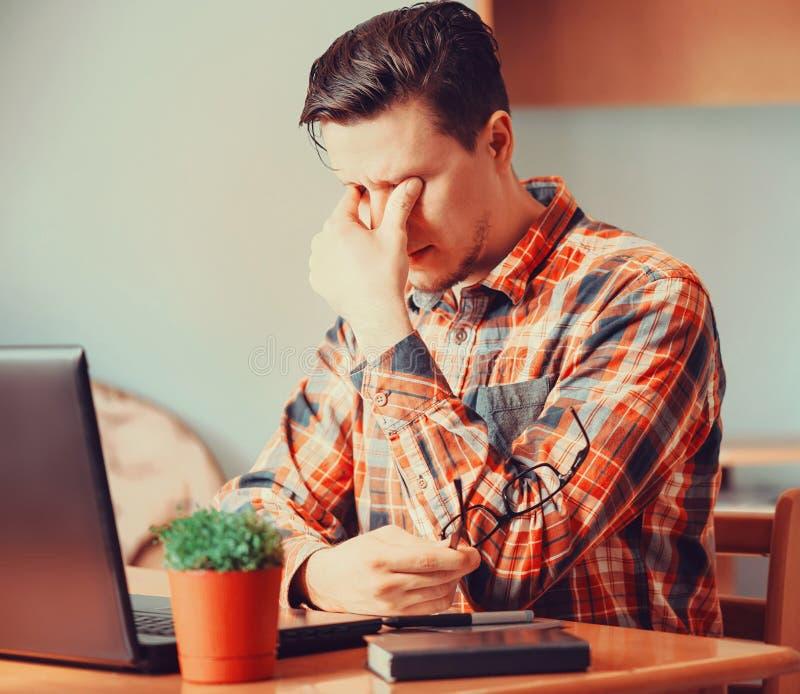 Homem cansado que senta-se sobre o portátil fotos de stock royalty free