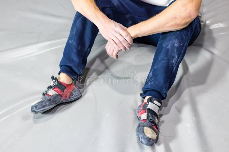 Homem cansado que toma o resto após ter escalado a parede bouldering em um gym de escalada da parede imagens de stock