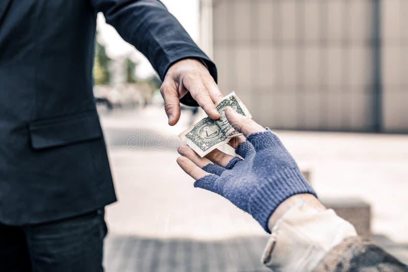 Homem caritativo no traje escuro do negócio que guarda para fora o dinheiro fotografia de stock