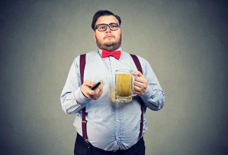Homem carnudo com a cerveja e a tevê remotas imagens de stock