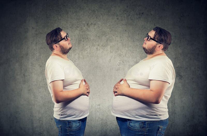 Homem carnudo novo que olha o sentimento da gordura ele mesmo bloated fotos de stock