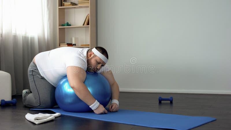 Homem carnudo que descansa após o exercício, encontrando-se na bola da aptidão, desejo perder o peso fotos de stock royalty free