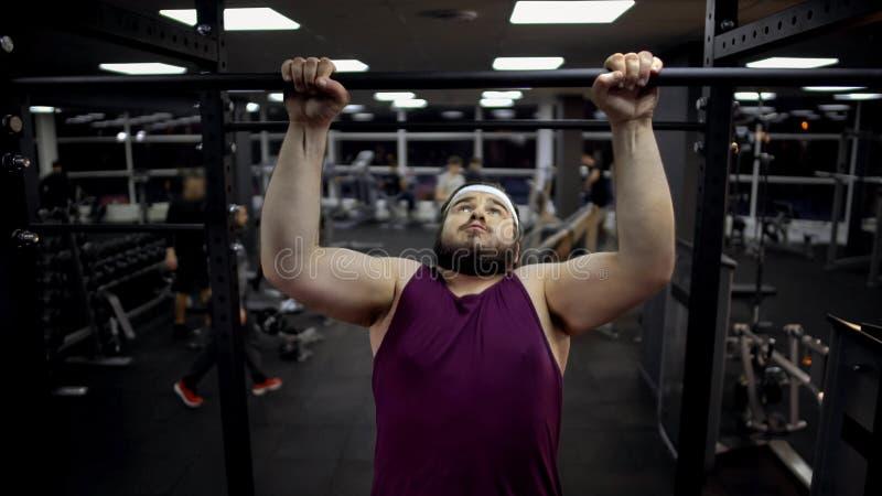 Homem carnudo que levanta na barra, desejo perder o peso e ser forte, motivação fotografia de stock royalty free