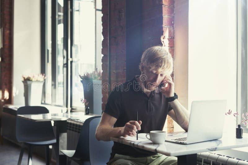 Homem caucasiano alegre com cabelo vermelho usando o computador e o smartphone que sentam-se no café que come o café Conceito de  fotografia de stock royalty free