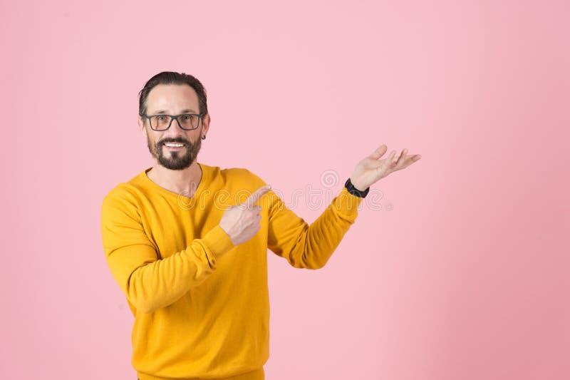 Homem caucasiano atrativo nos vidros com sorriso encantador largo O homem no casaco de lã mostra algo com a palma aumentada acima fotografia de stock